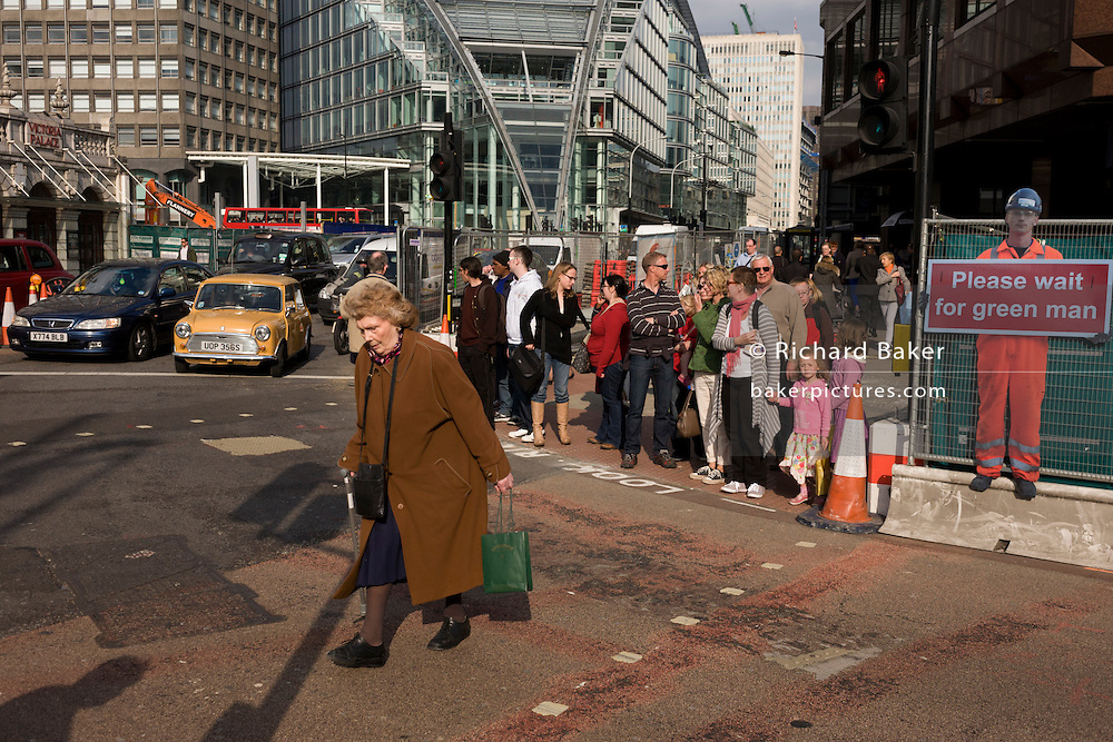 An elderly lady jaywalker crosses a road junction on a red pedestrian light in central London during temporary street improvements.