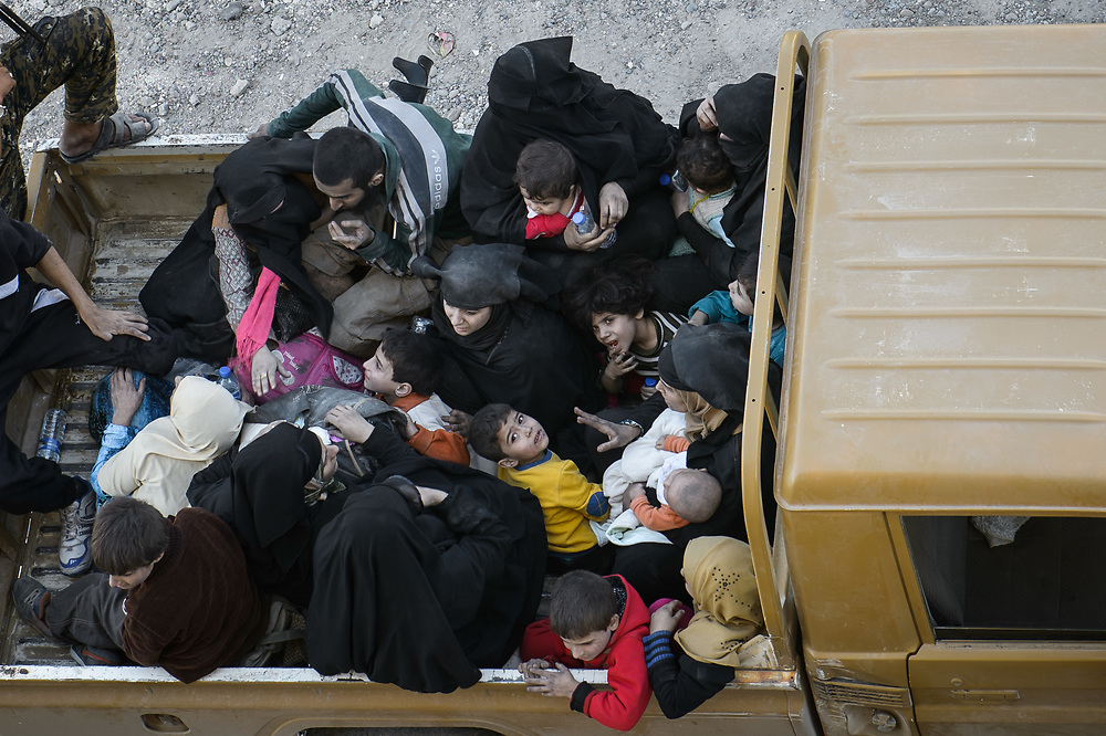 People from Raqqa sit in a pick-up of the SDF in eastern Raqqa. The SDF evacuated them from the Al-Badu neighborhood. They report that ISIS prevented them from fleeing. Raqqa,Syria,October12,2017