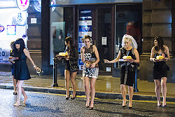 © Licensed to London News Pictures . 17/03/2013 . Manchester , UK . Women laden with takeaway pizzas and chips walk carefully across the road . Evening revellers out in the rain and snow in to the early hours , in Manchester this St Patrick's Day morning (17th March) . Photo credit : Joel Goodman/LNP