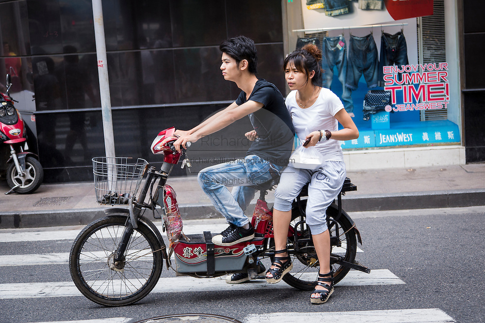 A young couple rides a scooter in Shanghai, China.