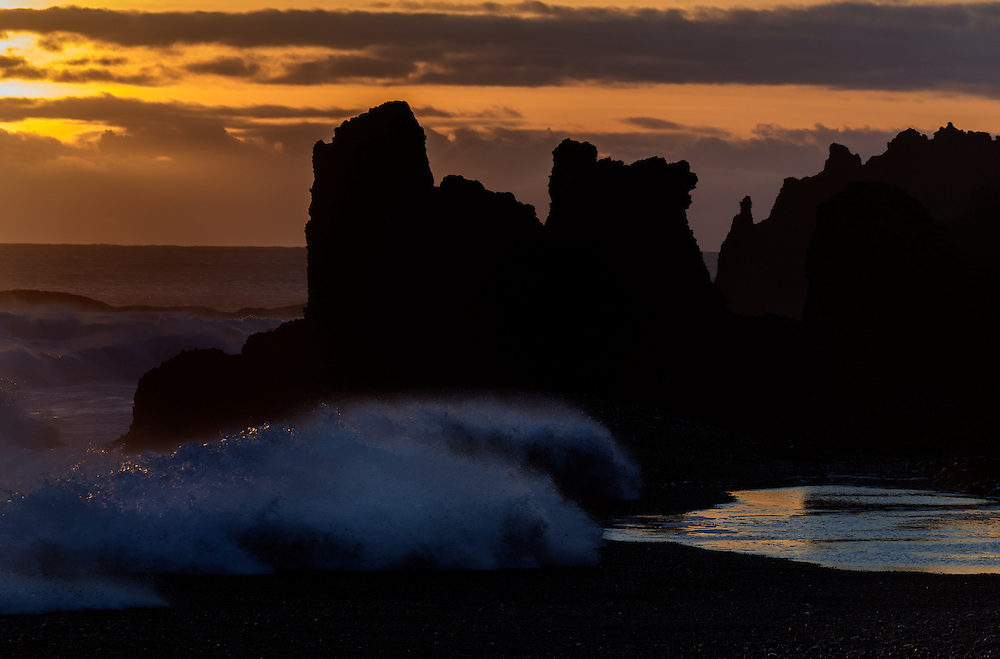 Peculiar rock formations and crashing waves on the black pebbled beach at sunset, Djúpalónssandur, Iceland
