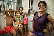 A Brazilian family in the Calabar Favela in Salvador, Brazil.  A favela is the Brazilian equivalent of a shanty town.  The majority have electricity, but in most cases it is illegally tapped from the public grid.  The Calabar favela is the oldest favela in Salvador, dating from 1913. Although it was originally built on the outskirts of the city, the city has grown around it, and it is now sandwiched between a rich and a middle class neighborhood.  Calabar is a shining example of community action.  There are no public schools in the favela, so the members of the community have organized their own. It receives no financial assistance from the government, subsisting on the proceeds from bake sales, donations, and grants from non-governmental organizations.