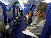passengers trying to sleep during flight in commercial airplane economy class