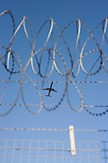 An airliner crosses the razor-wired perimeter fence at Heathrow Airport on its way to an international destination.