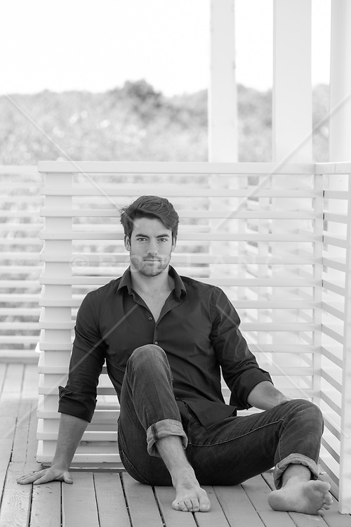 hot barefoot man sitting on a deck