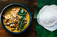Alleppey, India -- February 19, 2018: A traditional duck curry with appam.