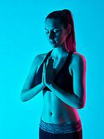 one caucasian woman zen portrait namaste salte yoga  in silhouette studio isolated on blue background
