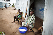 A woman cooks outside the basic shelter where she lives with her family at the Miketo IDP settlement, Katanga province, Democratic Republic of Congo on Sunday February 19, 2012.