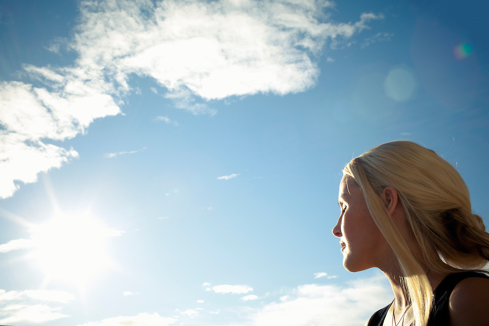 A young blond woman facing the sun