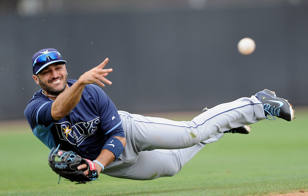 Tampa Bay Rays' Sean Rodriguez attempts to make a throw to third base after making a stop on a ground ball hit by Toronto Blue Jays' Jose Bautista in the fifth inning Friday, March 7, 2014 in Dunedin.