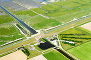 Nederland, Groningen, Gemeente Eemsmond, 05-08-2014; Noordpolderzijl met gemaal en uitwaterende sluis. Noordpolder ten noorden van Usquert.<br /> Bij het op deltahoogte brengen van de zeedijk is de oude sluis dichtgemetseld en deze maakt nu deel uit van het landart mozaiek.<br /> Noordpolderzijl pumping station and sluices. When the seawall was strengthened the old lock disappeared, it is now part of the landart mosaic. <br /> <br /> luchtfoto (toeslag op standard tarieven);<br /> aerial photo (additional fee required);<br /> copyright foto/photo Siebe Swart