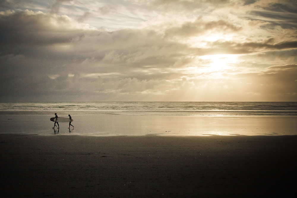 Two surfers walk with their surfboard on Muriwai Beach, New Zealand.
