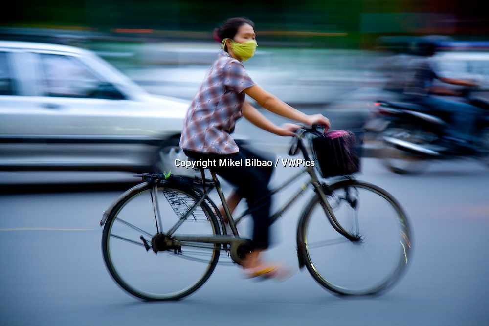 woman riding in a bicycle.<br /> Hanoi, Vietnam.