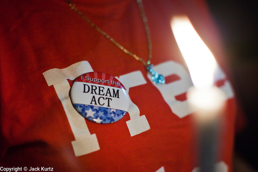 "Sept. 19 - PHOENIX, AZ: A woman wearing a button supporting the DREAM Act at a candlelight vigil at Sen. John McCain's office in Phoenix Sunday. About 30 people met in front of US Sen. John McCain's office in Phoenix Sunday night to demonstrate in support of the DREAM Act, which is scheduled to be debated in the US Senate on Tuesday, Sept 21. The Development, Relief and Education for Alien Minors Act (The ""DREAM Act"") is a piece of proposed federal legislation in the United States that was introduced in the United States Senate, and the United States House of Representatives on March 26, 2009. This bill would provide certain illegal immigrant students who graduate from US high schools, who are of good moral character, arrived in the U.S. as minors, and have been in the country continuously for at least five years prior to the bill's enactment, the opportunity to earn conditional permanent residency. In the early part of this decade McCain supported legislation similar to the DREAM Act, but his position on immigration has hardened in the last two years and he no longer supports it. The protesters, mostly area students, marched and drilled to show their support for the US military and then held a candle light vigil.   Photo by Jack Kurtz"