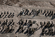 An aerial view of a local graveyard near Cape Town. The early morning shadows adding a classic, yet sombre tone to the stones reflecting the end of life. One of four aerial images making up the exhibited series of art photography, titled 'One Day, One Life'. Limited edition prints available for sale by Greg Beadle.