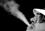 Jonathan Goodrum, of Pittsburgh, PA, smokes while waiting for players on No. 16 during the second round of the Masters at Augusta National Golf Club in Augusta, GA.