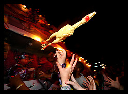 Feb 26th, 2006. New Orleans, Louisiana. The Krewe of Bacchus rolls during Mardi Gras. Crowds pack the route along Napoleon Avenue screaming for beads from the floats. Beads fly along with other items such as rubber chickens to the delight of the family packed crowds. Children are handed soft toys as they party continues in ernest in New Orleans.
