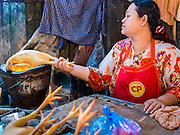 """03 APRIL 2014 - BANGKOK, THAILAND:  A vendor scorches chickens over a fire to remove the feathers in Khlong Toey Market. Khlong Toey (also called Khlong Toei) Market is one of the largest """"wet markets"""" in Thailand. The market is located in the midst of one of Bangkok's largest slum areas and close to the city's original deep water port. Thousands of people live in the neighboring slum area. Thousands more shop in the sprawling market for fresh fruits and vegetables as well meat, fish and poultry.     PHOTO BY JACK KURTZ"""