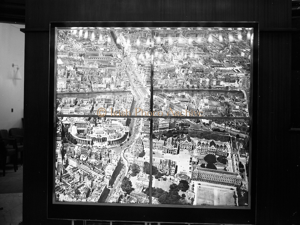 24/01/1962<br /> 01/24/1962<br /> 24 January 1962<br /> Illuminated map at Ulster Bank, College Green, Dublin. A large hand coloured illuminated photograph depicting the principal feature of central Dublin was put on display in Ulster Bank. It was an aerial view of the city centre enlarged to five feet by five feet nine inches from a transparency of 5 by 4 inches. The bank felt that it would be of interest to customers and tourists alike.