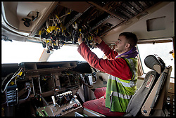 Plane Dismantler Ben Hopper takes the cockpit of an A340 apart at Air Salvage International in Cirencester, Cotswold,United Kingdom, Friday, 15th November 2013. The Planes at the Aeroplane Scrapyard are taken apart for spare parts and scrap. In the air, A plane could be worth around £12.5M, But as parts it might be worth almost £19M. Almost everything on a modern airliner can be recycled, except the light bulbs and tyres. More than 40 planes are recycled at Air Salvage a year. Picture by Andrew Parsons / i-Images