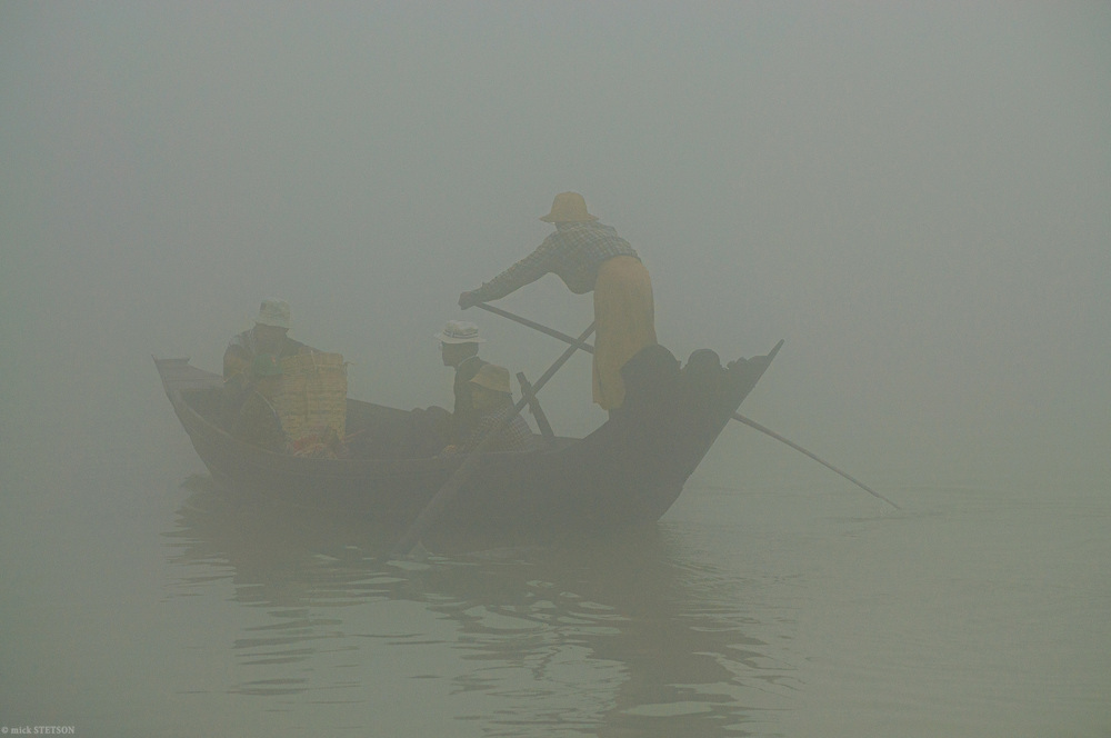 — Early morning fog from the Pathein River envelops an oarsman and his passengers as they take their goods downriver to neighboring villages.