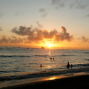 Waikiki Beach at sunset is one of the most famous beaches in the world. The two mile stretch of white sand coast is fronted by hotels and tourist facilities in Honolulu, Hawaii.. <br />