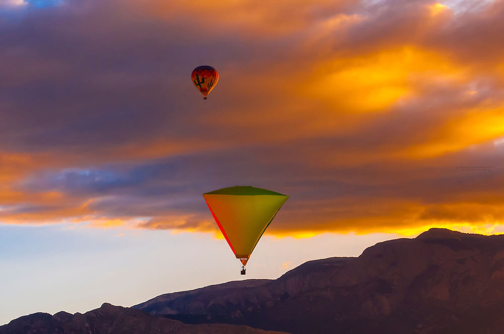 A special shapes hot air balloon flying at sunrise (with the Sandia Mountains in background) during the Albuquerque International Balloon Fiesta, Albuquerque, New Mexico USA.