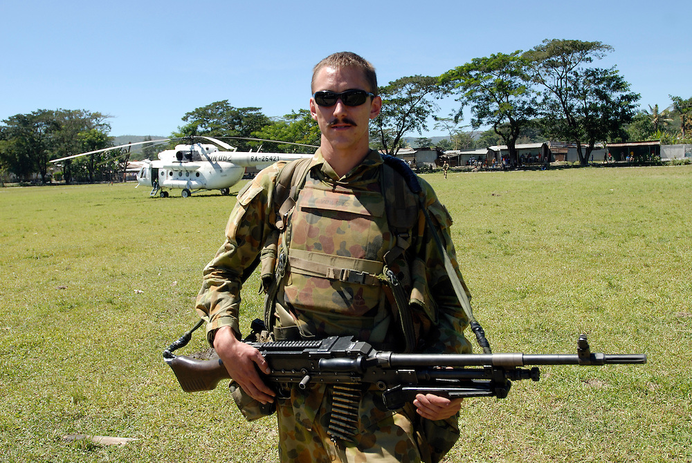 An Australian Peace Keeper guards a UN helicopter as UN Officials and members of the Media visit a polling staion in Gleno where voters cmake their between both candidates for East Timor's Presidential Elections.
