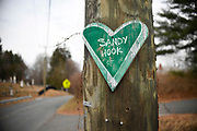 A small green wooden heart is nailed to a telephone poll near Sandy Hook School, Saturday, Dec. 2, 2017, in Newtown, Conn.   Makeshift memorials are long gone with only subtle touches in town of 12/14.(Jessica Hill for the New York Times)
