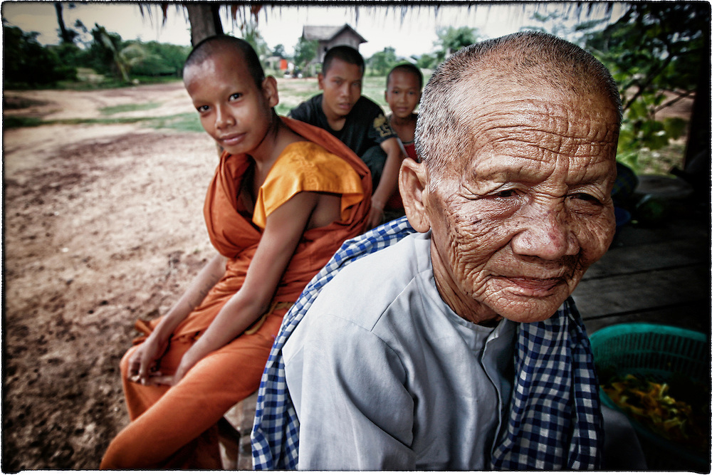 A Cambodian Buddhist nun sits with a Buddhist monks and others in Ang Long Veng, the former stronghold of Khmer Rouge leader Pol Pot.