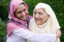 Young female carer embracing an older woman,