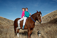 Twin sisters riding horseback double, South Dakota, <br /> MODEL RELEASED