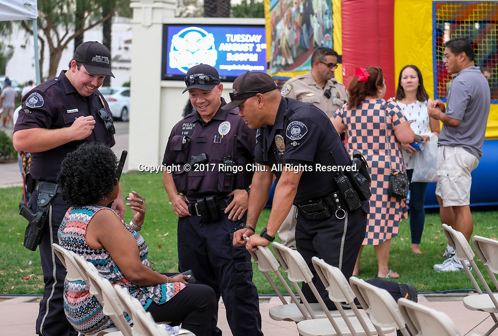 Police officers smile chatting with a participant during National Night Out in San Gabriel, California, on Tuesday, Aug. 1, 2017. National Night Out is a community-police awareness-raising event in the United States and Canada, held the first Tuesday of August. Texas and Florida have the option to use the alternate date of the first Tuesday in October to avoid hot weather.(Photo by Ringo Chiu)<br /> <br /> Usage Notes: This content is intended for editorial use only. For other uses, additional clearances may be required.