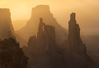 Golden sunrise glow silhouettes the Washer Woman Arch, Mesa Arch, Canyonlands National Park, Utah