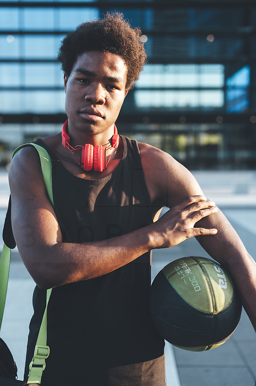 Young afro man trining basketball in urban scenery