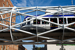 Modern public tram running on modern architectural steel truss bridge in centre of The Hague in The Netherlands