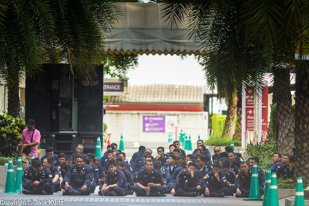 "01 JUNE 2014 - BANGKOK, THAILAND: Thai police sit in the shade and wait to deploy during an anti-protest security operation in the Ratchaprasong district in Bangkok. The Thai army seized power in a coup that unseated a democratically elected government on May 22. Since then there have been sporadic protests against the coup. The protests Sunday were the largest in several days and seemed to be spontaneous ""flash mobs"" that appeared at shopping centers in Bangkok and then broke up when soldiers arrived. Protest against the coup is illegal and the junta has threatened to arrest anyone who protests the coup. There was a massive security operation in Bangkok Sunday that shut down several shopping areas to prevent the protests but protestors went to malls that had no military presence.    PHOTO BY JACK KURTZ"