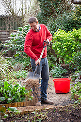 Resurfacing a path by spreading gravel, raking it even and tamping it down