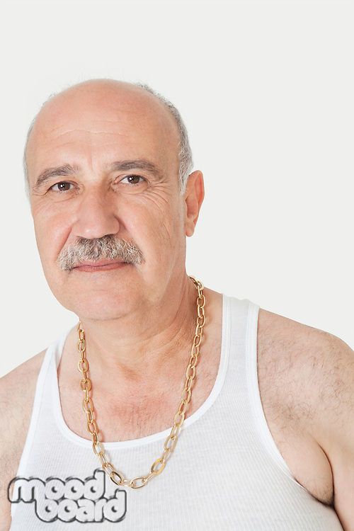 Portrait of senior man in vest with gold chain over gray background