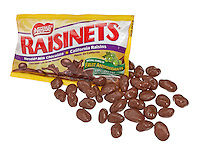a few loose Raisinets on a white background with the packaging