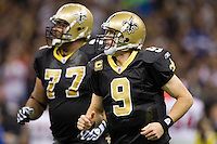 28 November 2011: Quarterback (9) Drew Brees of the New Orleans Saints runs off the field with his teammate (77) Carl Nicks while playing against the New York Giants during the first half of the Saints 49-24 victory over the Giants at the Mercedes-Benz Superdome in New Orleans, LA.