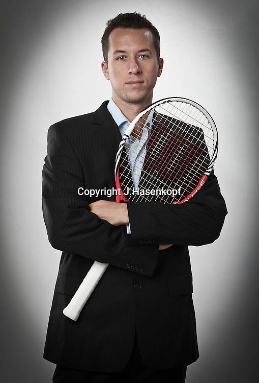 Tennis Profi Philipp Kohlschreiber(GER)steht im dunklen Anzug und haelt einen Tennissschlaeger,Fotostudio,<br /> laessige Pose,Einzelbild,<br /> Hochformat,Halbkoerper,