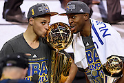 Stephen Curry #30 and Andre Iguodala #9 of the Golden State Warriors celebrate with the Larry O'Brien NBA Championship Trophy after defeating the Cleveland Cavaliers in Game Six of the 2015 NBA Finals at Quicken Loans Arena on June 16, 2015 in Cleveland, Ohio.