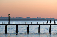3 tourists watching the sunset at the White Rock Pier in White Rock, British Columbia, Canada.  Photographed from White Rock Beach looking west across Boundary Bay towards the mountains on Vancouver Island.