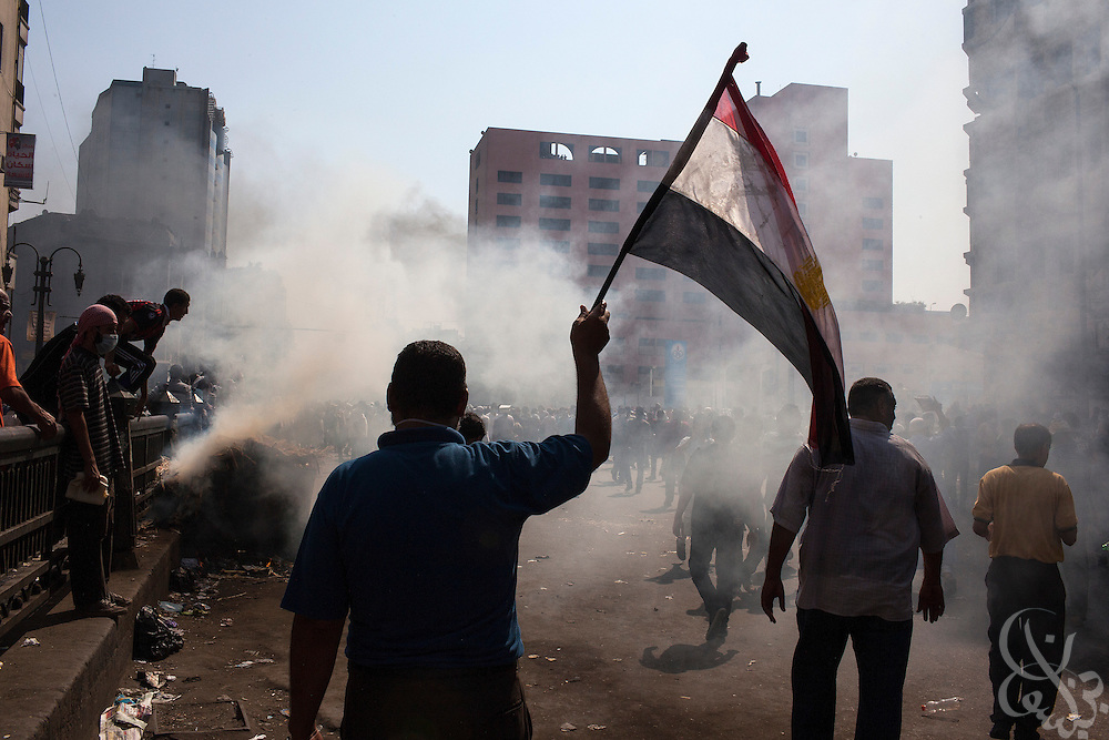 An Egyptian supporter of deposed Egyptian President Mohamed Morsi waves the Egyptian flag as teargas and smoke flow past during street clashes in the Ramses Square area of Cairo August 16, 2013.
