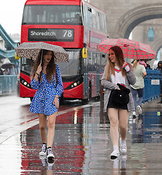 © Licensed to London News Pictures. 10/08/2018. London, UK.  Tourists during a heavy rain shower and wet weather on Tower Bridge at lunchtime today.  Photo credit: Vickie Flores/LNP