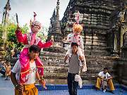 "05 APRIL 2015 - CHIANG MAI, CHIANG MAI, THAILAND:  Boys and their family member attendants in front of the chedi (stupa) on the second day of the three day long Poi Song Long Festival in Chiang Mai. The Poi Sang Long Festival (also called Poy Sang Long) is an ordination ceremony for Tai (also and commonly called Shan, though they prefer Tai) boys in the Shan State of Myanmar (Burma) and in Shan communities in western Thailand. Most Tai boys go into the monastery as novice monks at some point between the ages of seven and fourteen. This year seven boys were ordained at the Poi Sang Long ceremony at Wat Pa Pao in Chiang Mai. Poy Song Long is Tai (Shan) for ""Festival of the Jewel (or Crystal) Sons.    PHOTO BY JACK KURTZ"
