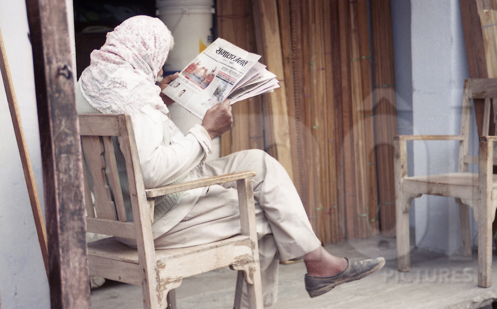 An old man sits on a wooden chair and reads newpaper. Jaipur, India ...