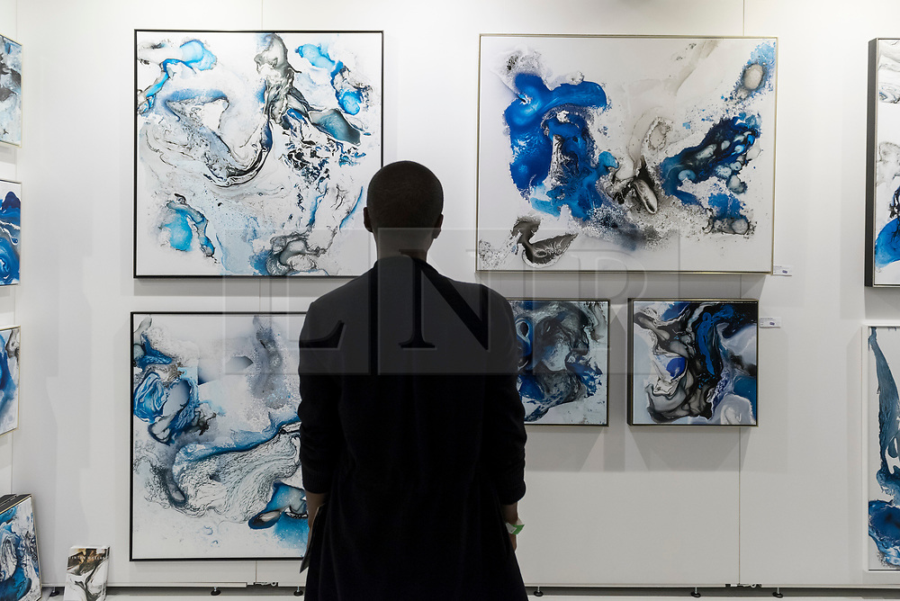 © Licensed to London News Pictures. 05/10/2018. LONDON, UK. A visitor views polymer artworks by Fintan Whelan. Opening day of The Other Art Fair, presented by Saatchi Art, which runs until 7 October in Bloomsbury.  The fair, which coincides with Frieze Week, is a collection of artworks by independent and emerging artists handpicked by a committee of art world experts.  Visitors and art buyers have the opportunity to meet the artists presenting their work at the fair. Photo credit: Stephen Chung/LNP