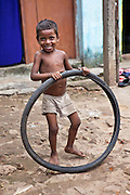 A young boy from the Pilgrim Roam slum plays with an old bicyle tyre. Orissa District, India.